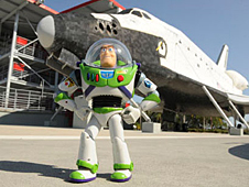 Buzz Lightyear standing in front of a space shuttle orbiter