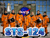 Seven astronauts in orange launch and entry suits stand behind the words STS-124