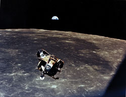 Welcome sight - With a half-Earth in the background, Apollo 11 command module pilot Michael Collins photographs the lunar module ascent stage shortly before his reunion with moonwalkers Neil Armstrong and Buzz Aldrin.