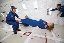 Reduced gravity test - Astronaut Dottie Metcalf-Lindenburger, then an astronaut candidate, experiences a moment of reduced gravity while flying in a KC-135 aircraft over the Gulf of Mexico in 2004. Assisting Metcalf-Lindenburger is Reduced Gravity Office lead test director John Yaniec. In the background are Dottie's fellow astronaut candidates Randy Bresnik and Jose Hernandez, now NASA astronauts.