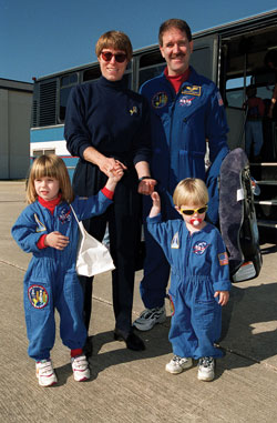 Family ties - Space shuttle Discovery (STS-103, Dec. 1999) mission specialist John Grunsfeld, with his wife Carol and their children, Sarah and Mace, pose for the camera on the runway at Patrick Air Force Base in Cocoa Beach, Fla.