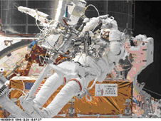 Astronauts working on the Hubble in space while Hubble is attached to the space shuttle.