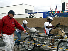 Tom Hancock walking alongside a moonbuggy and team on the track