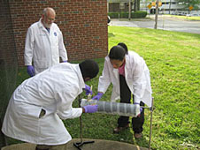 Rudy Gostowski looks on as students prepare a part of their rocket