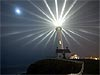Picture of lighthouse giving off light against a dark sky with the moon in the background