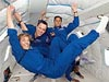Three educator astronauts in blue flight suits floating in an airplane