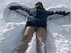 A girl lying in the snow making a snow angel