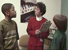An audiologist speaks with two students
