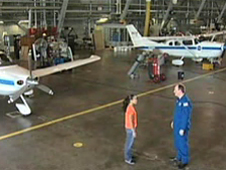 A student talks with a pilot in an airplane hangar