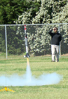 A rocket leaves a launch pad as a man watches