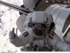 Hadfield, wearing a white spacesuit, holds up one thumb while working outside the space station