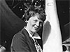 Amelia Earhart stands next to the propeller of a plane