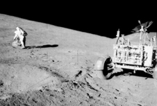 Roving Hadley Delta - Apollo 15 astronaut David R. Scott studies a boulder on the slope of Hadley Delta during one of three long excursions using the lunar rover in July-August 1971.