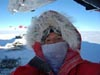 Tia Ferguson in a red coat with a furry hood in Antarctica
