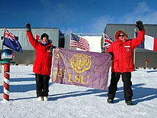 Tia Ferguson and Joachim Isbert hold the purple and gold LSU flag at the Ceremonial South Pole