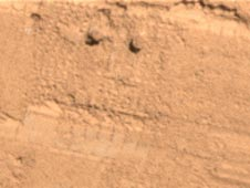 two holes at the top created by the lander's Robotic Arm's motorized rasp tool