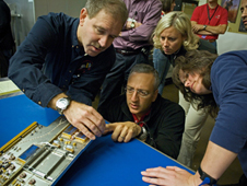Astronauts John Grunsfeld (left) and Mike Massimino inspect position indicator decals on the STIS replacement printed circuit board