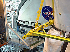 Technicians observing the orbiter being moved into place in the VAB