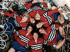 Crew members floating in a circular pattern inside the space shuttle