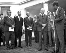Legendary leader - Alan Shepard, John Glenn, and James Webb (behind microphones) look on as President John F. Kennedy presents Dr. Robert Gilruth, director of the Manned Spacecraft Center, Houston, Texas, with the Medal for Distinguished Federal Civil Service. The ceremony took place on the White House Lawn.