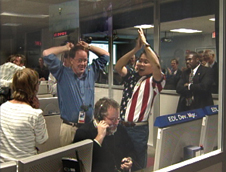 Jumping for joy - Above-Richard Cook, Mars Exploration Rover (MER) deputy project manager and Wayne Lee, MER chief engineer for the rovers' descent and landing systems, jump for joy when the word reached the Jet Propulsion Laboratory that Spirit had successfully landed on the Red Planet on Jan. 3, 2004. Sitting at the control desk is Rob Manning, entry, descent and landing operations manager.