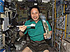 Astronaut Ed Lu uses chopsticks to hold food while a drink packet floats by