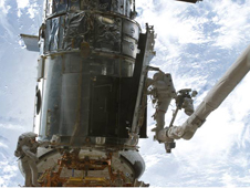 Astronaut on shuttle robotic arm working on the Hubble during a previous servicing mission