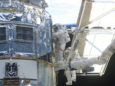 Two astronauts work on the Hubble during a a previous servicing mission in 2002