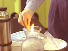 A woman places a lit match into a glass container