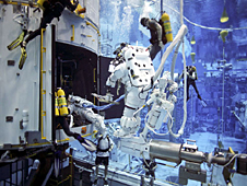SCUBA divers work with astronauts in a large pool of water
