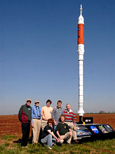 The team of students and mentors in front of an Ares I model