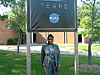 Kim Terrell standing underneath a sign with the NASA 50th anniversary logo