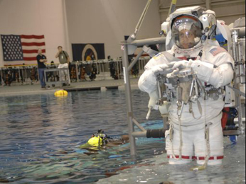 HST SM4 astronaut Mike Massimino enters the water at the NBL.