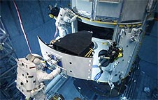 Astronauts practice installing the Wide Field Camera 3 during a training session in an underwater facility