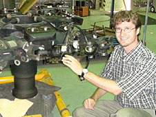 Marr kneels beside UH-60A Black Hawk helicopter hub hardware