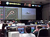 Mission controllers look at video monitors of the shuttle landing