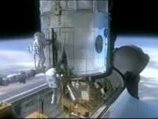 image from animation of astronauts working on Hubble while it is docked in the shuttle