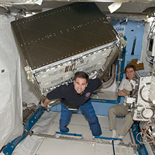 iss017e014091 -- Greg Chamitoff appears to carry a huge load though microgravity renders the experiment rack weightless