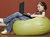 Young girl on a beanbag looking at a laptop computer on her lap