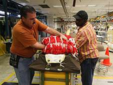 Workers carefully fold parachute