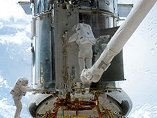 Astronauts working on the Hubble. One is on the robotic arm.