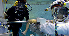 An astronaut uses a power tool during training in the Neutral Buoyancy Lab