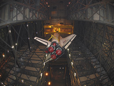 Space shuttle Endeavour is lifted inside the Vehicle Assembly Building.
