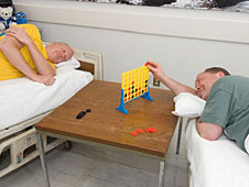 Two bed rest study participants lying in beds and playing a game