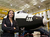 A woman stands in front of a shuttle simulator