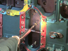 Close-up of an astronaut's hand removing screws from the cover of STIS with the fastener capture plate