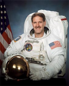 Grunsfeld in a white spacesuit, holding his helmet