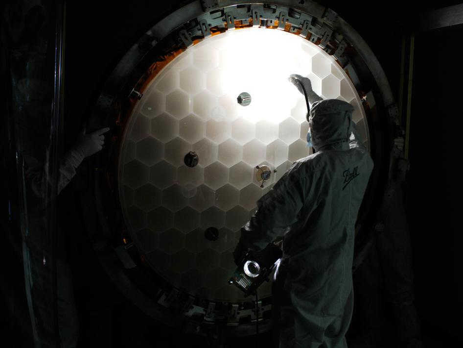 Inspection of the primary mirror honeycomb structure. The mirror has been 86% light weighted. That is it only weighs 14% (1/7) that of a solid mirror of the same dimensions. The mirror blank was made by Corning Glass works out of ULE, ultra-low expansion glass. The optical polishing of the mirror was performed by Brashear LP.