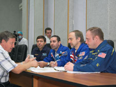 Michael Barratt, Nik Halik, Richard  Garriott and Michael Fincke discuss flight data file information with trainer