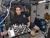 Greg Chamitoff floats next to a chess board on the space station